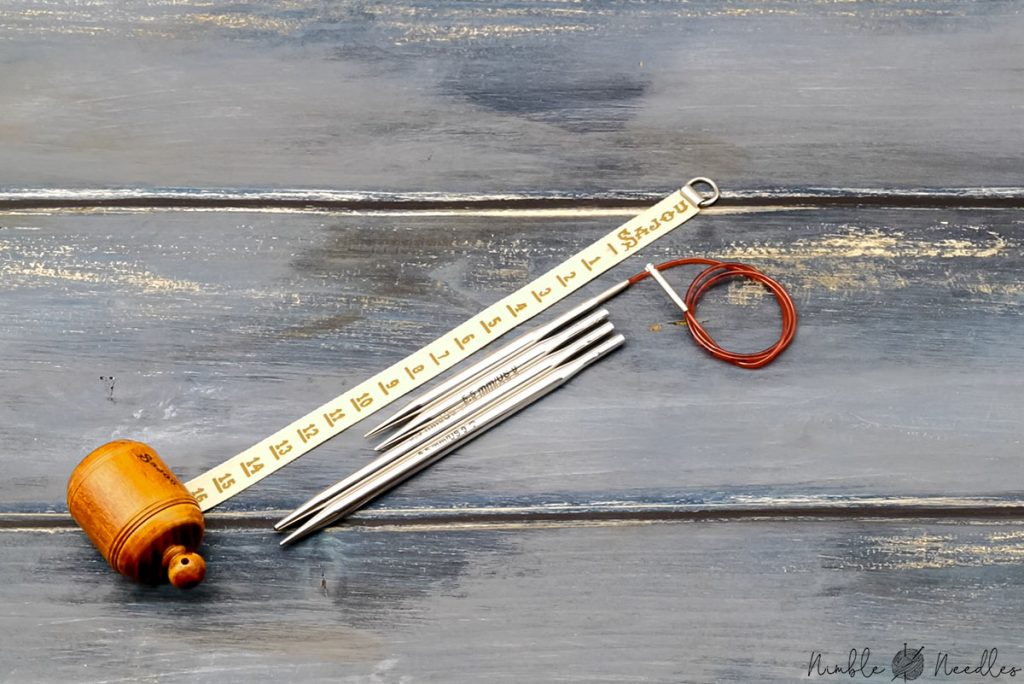 the short version of the addi click interchangeable knitting needles compared to the standard size and a measuring tape next to it to show the size