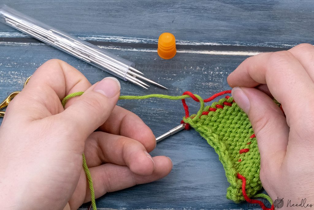 tying a knot after you finished knitting one row in a new color to secure the first stitch