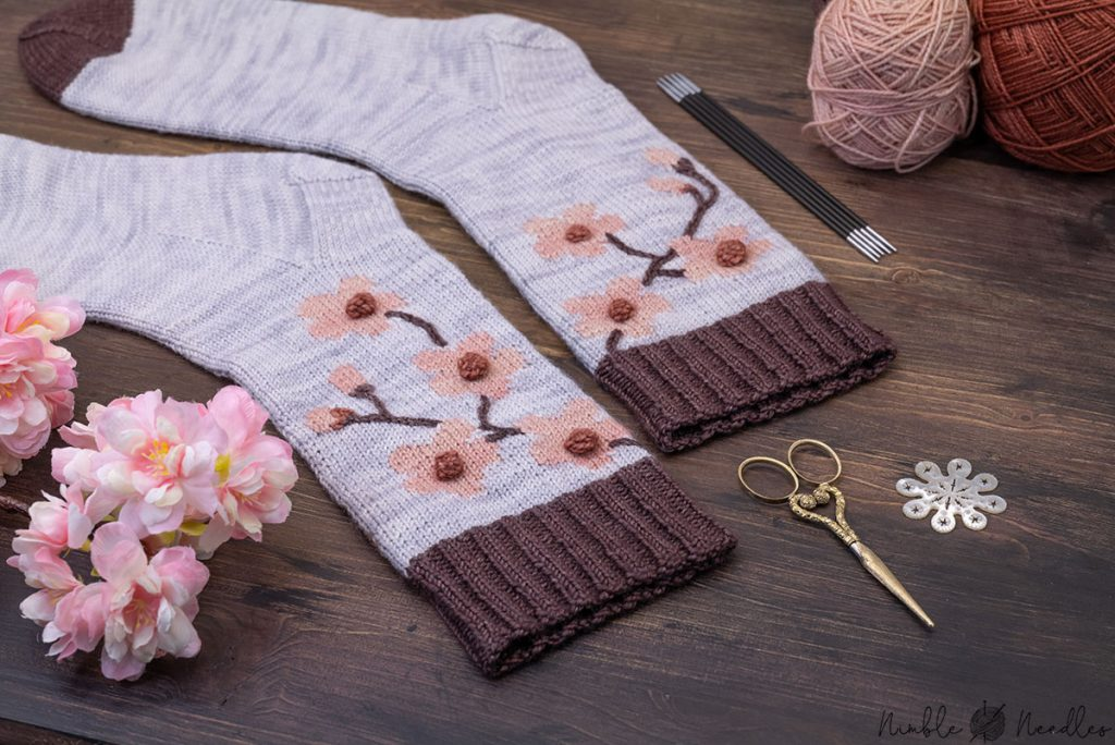 detail shot of the cherry blossom socks with various knitting tools in the background
