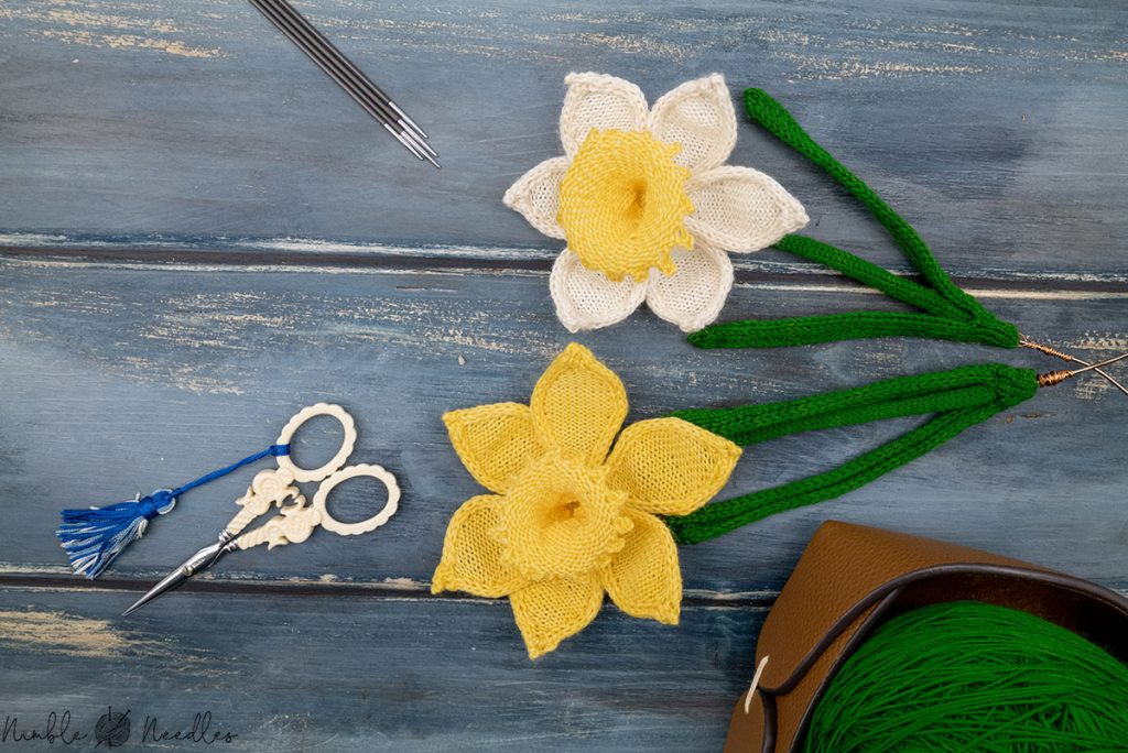 two knitted daffodil on a wooden board