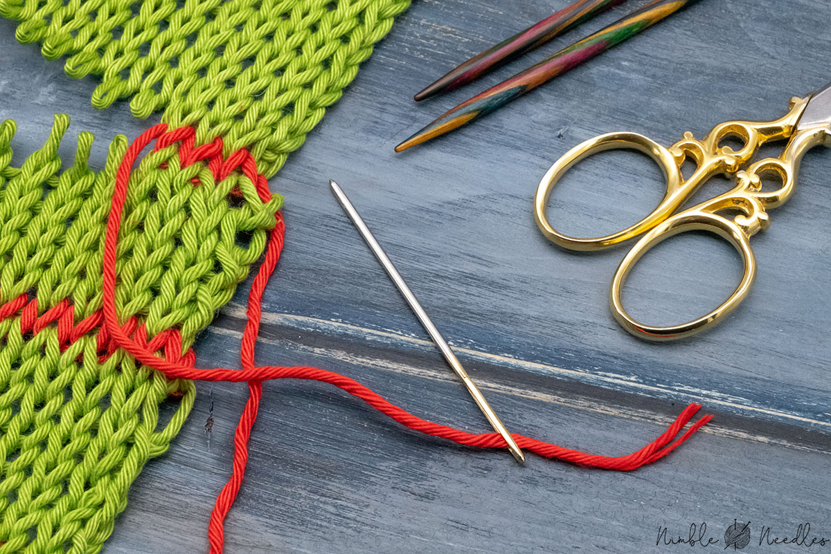 grafting knitting stitches with a tapestry needle (and various knitting tools in the background)