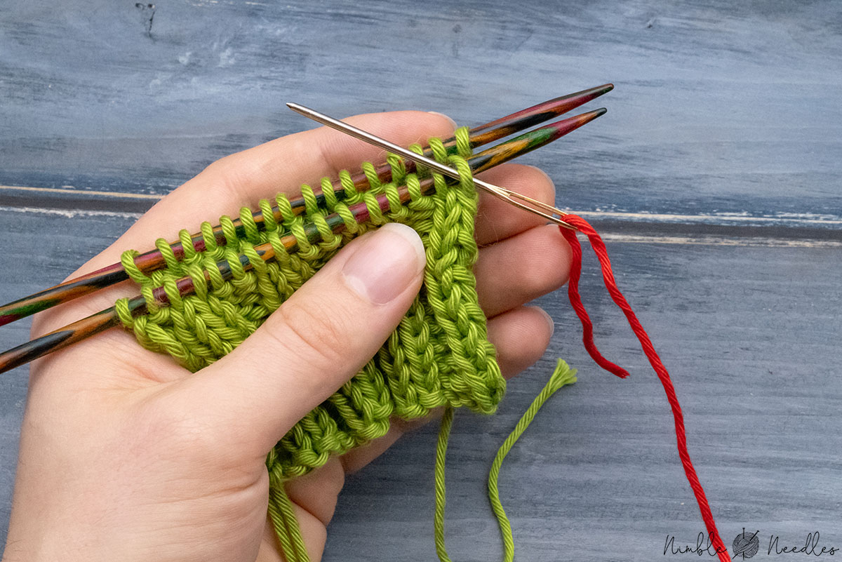 going into the first stitch on the first needle purlwise
