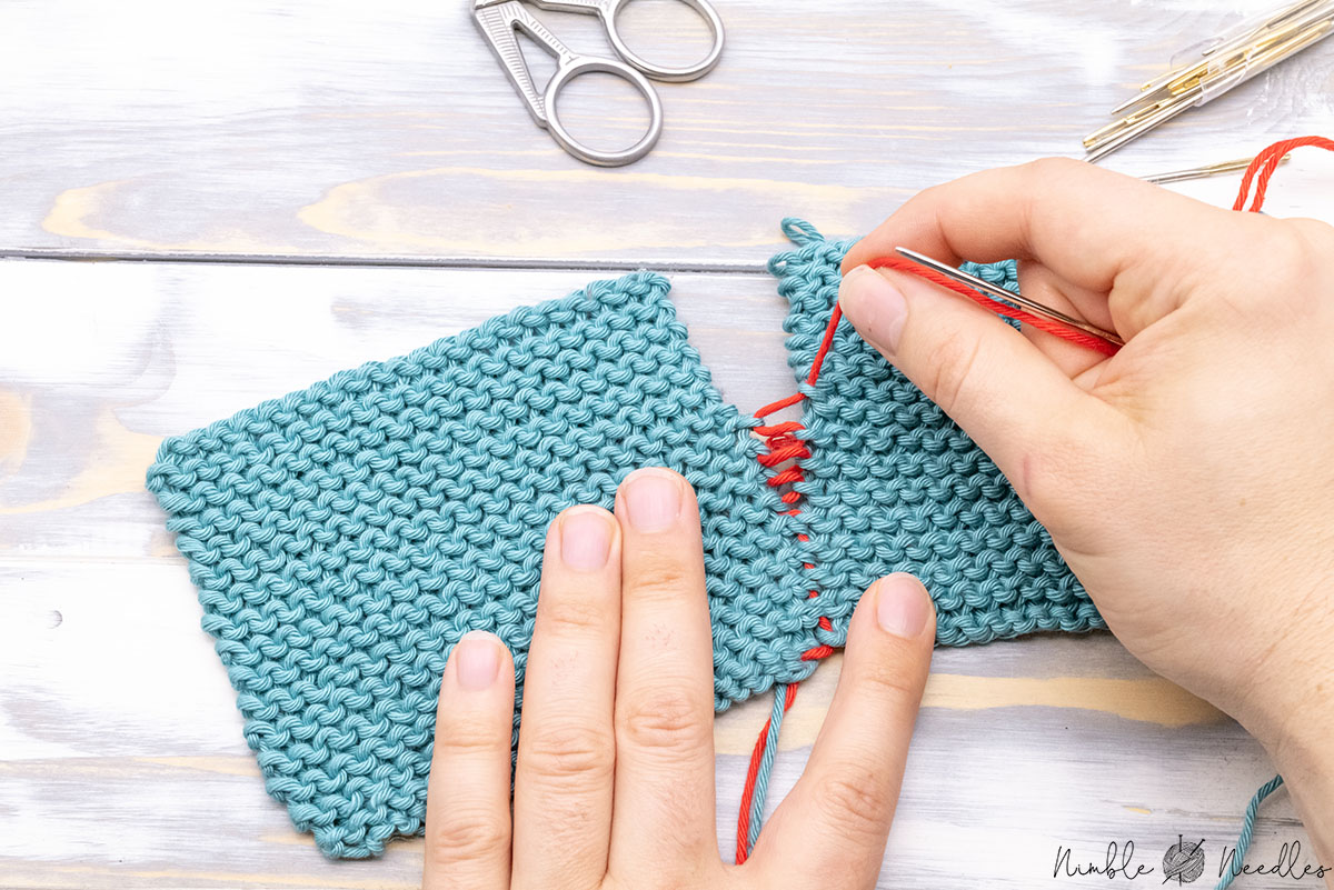 joining knitted pieces in garter stitch together with the mattress stitch and someone pulling on the tail to close the seam