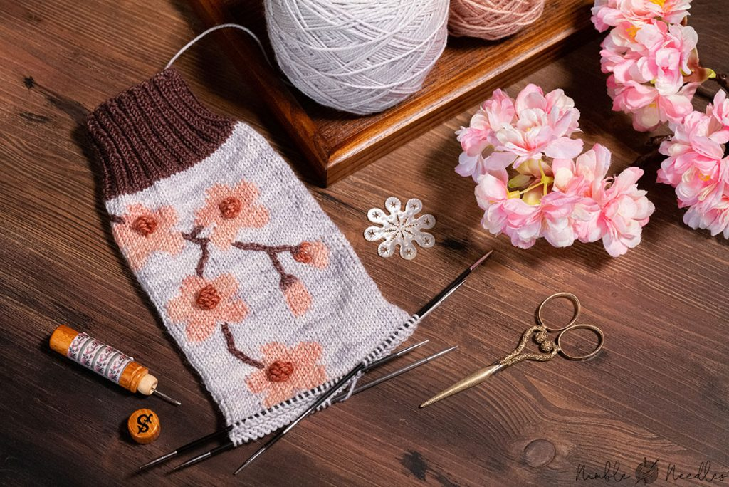 the cherry blossom intarsia socks still on the needle