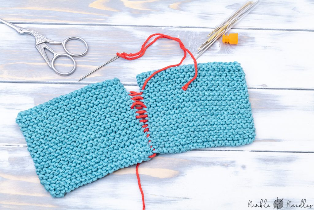 seaming garter stitch with the mattress stitch using a red contrasting yarn