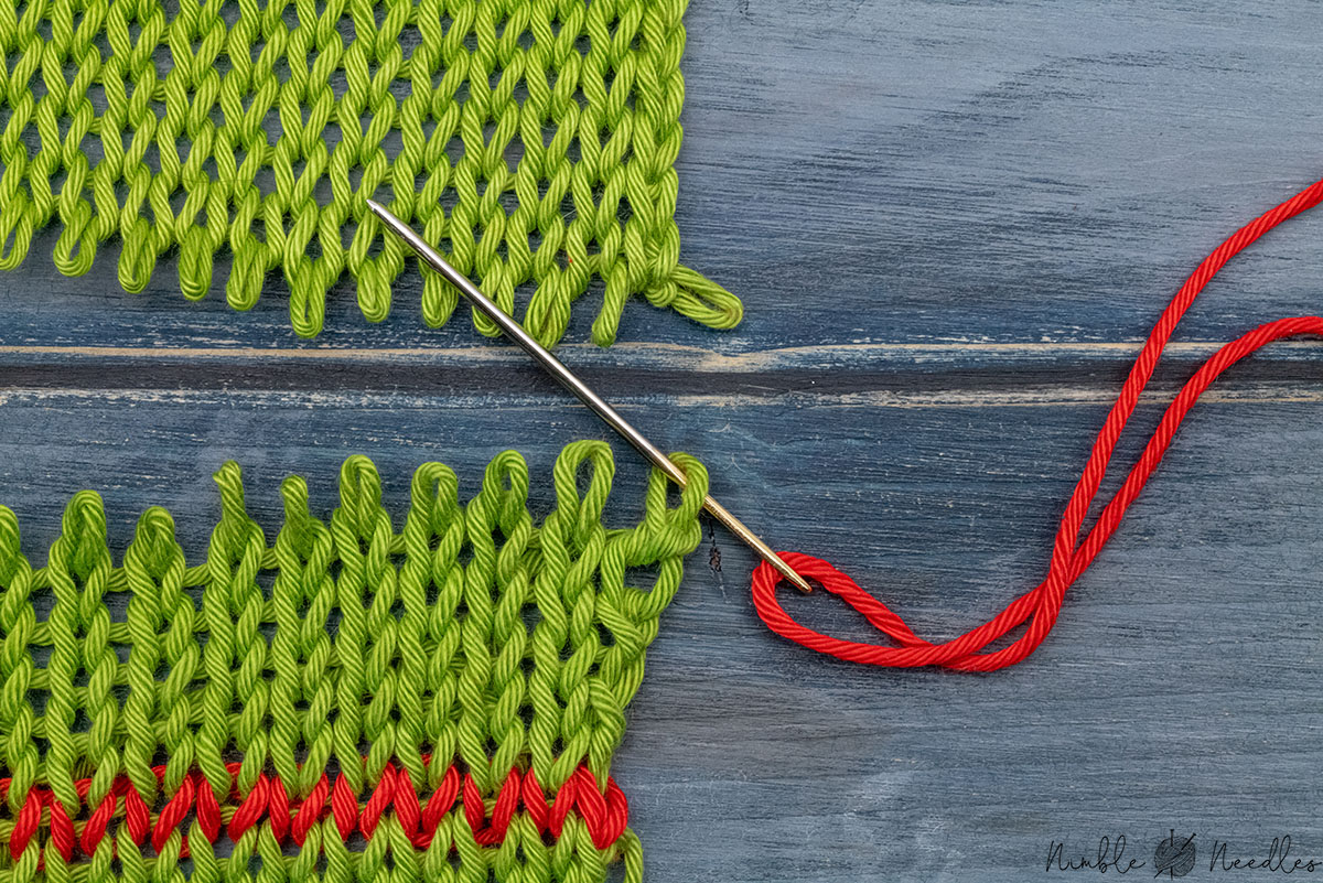 going through the first stitch on the bottom from behind to start grafting knitting stitches