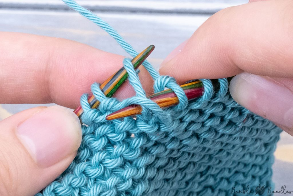 inserting the left needle into the dropped stitch from behind going underneath the strand