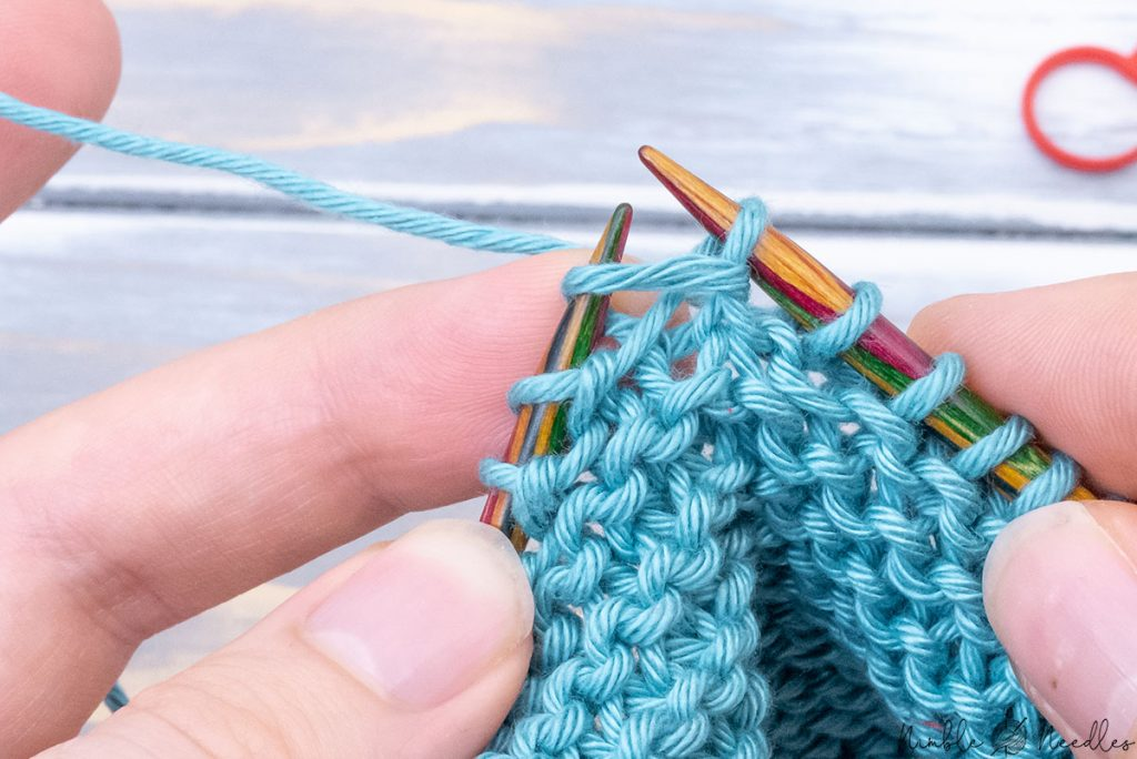 pulling the yarn/dropped strand all the way through with your right knitting needle