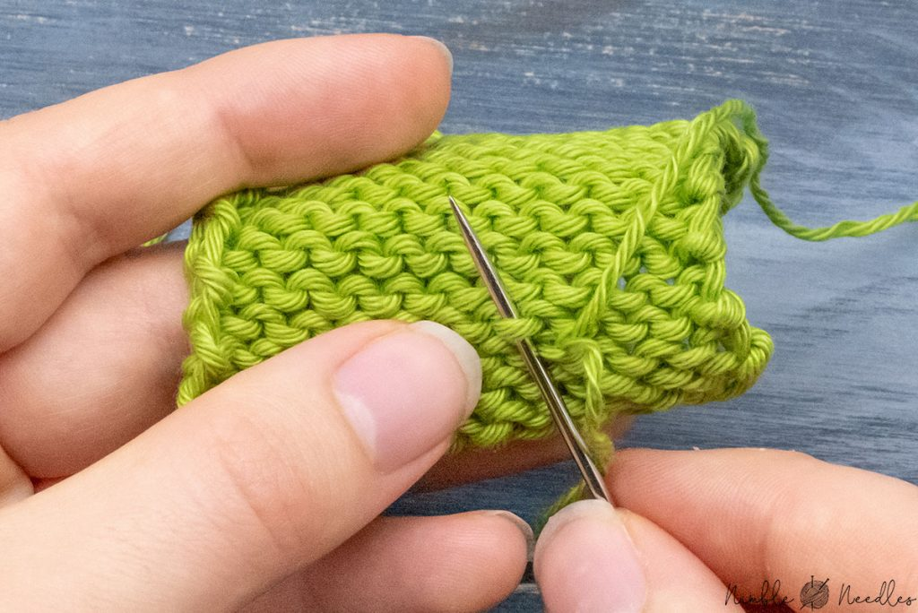 going underneath the bump of a purl stitch with one part