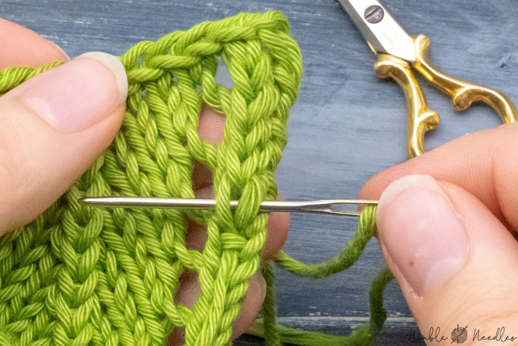 going underneath the two legs of knit stitch