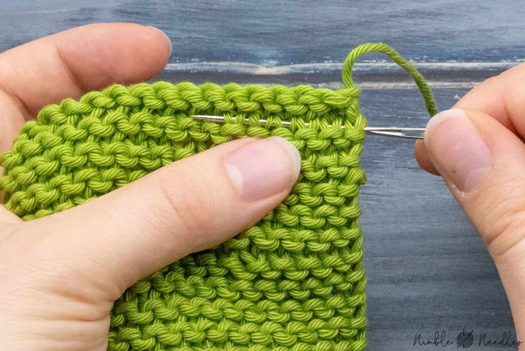 weaving in the tails of garter stitch by pulling the yarn through the legs of the knit stitches with a tapestry needle