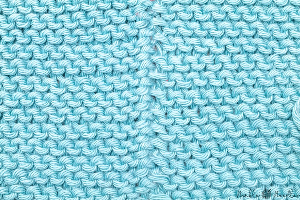 wrong side of the garter stitch seam where you can barely see a ridge