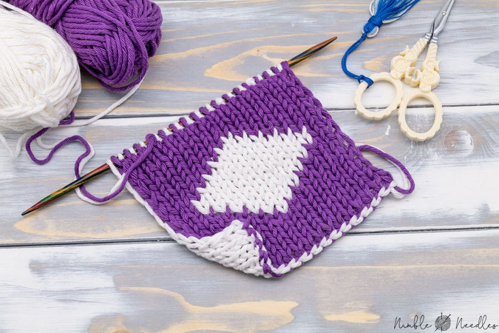 a double knitting project still on the needles with one side in white and the other side in purple