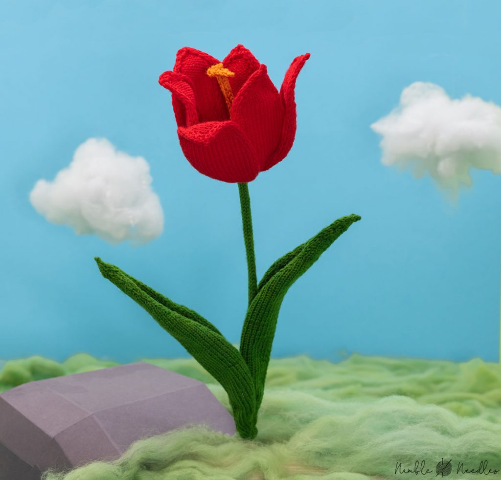 a red knitted tulip in a diorama made of wool roving and cotton candy clouds