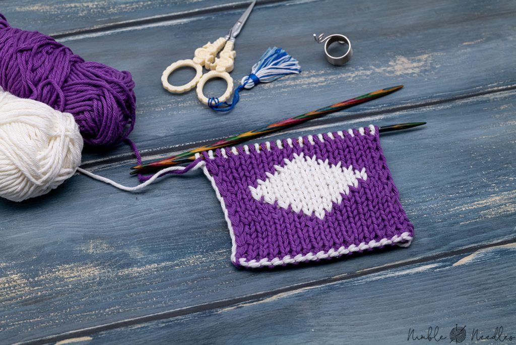 a swatch knitted with the double knitting technique with various tools in the background