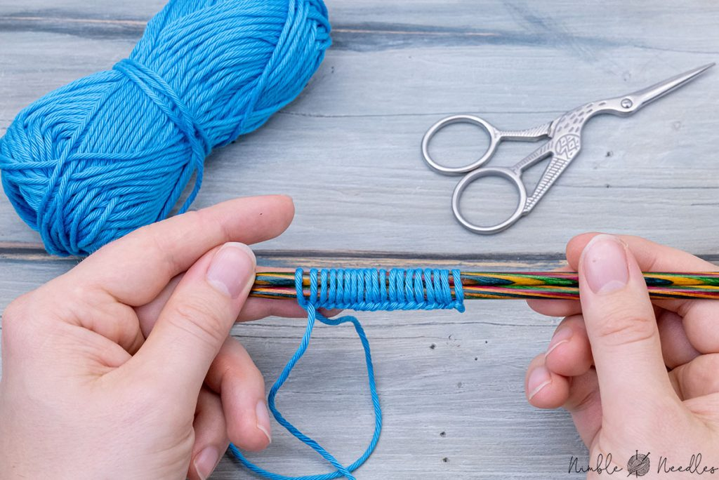 casting on stitches with two needles - someone holding it up with their fingers
