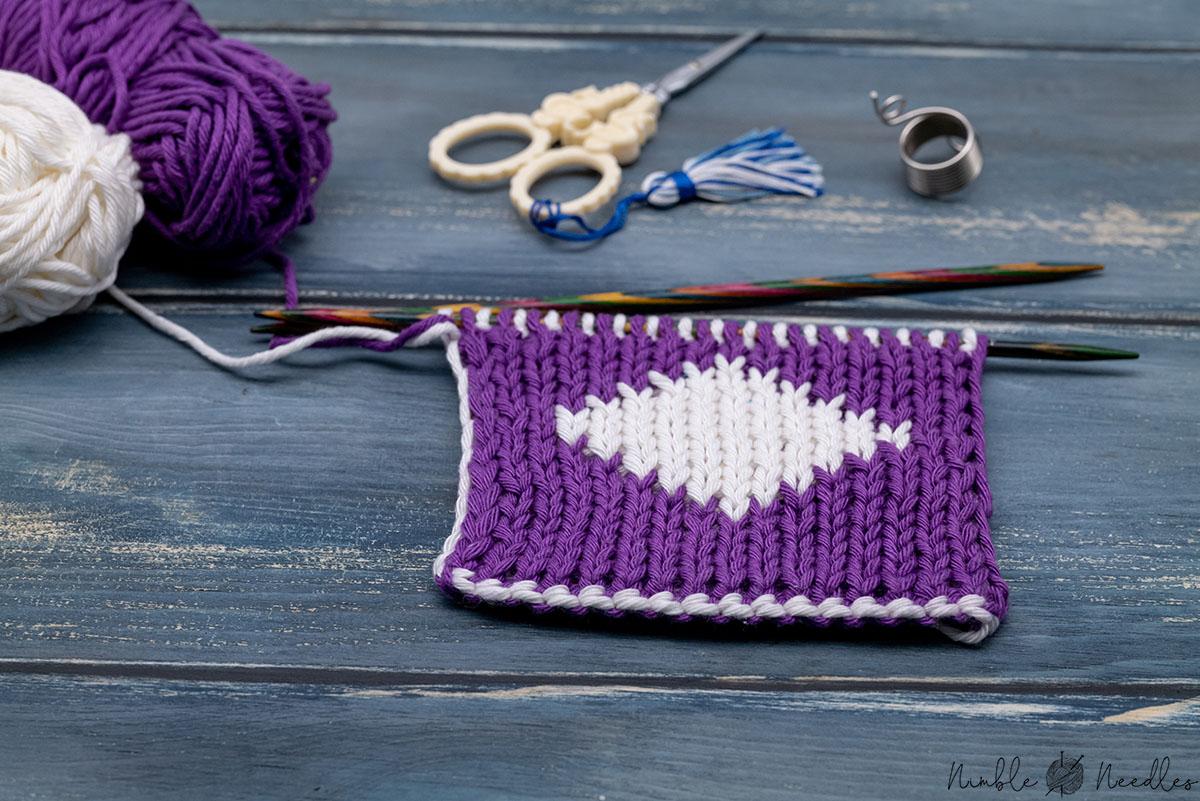close-up of a double knitting swatch using two colors on a wooden board