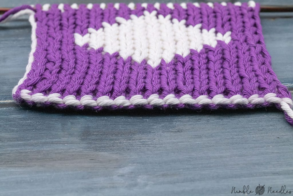 closeup of the edge created by two colored cast on double knitted on a swatch in white and purple