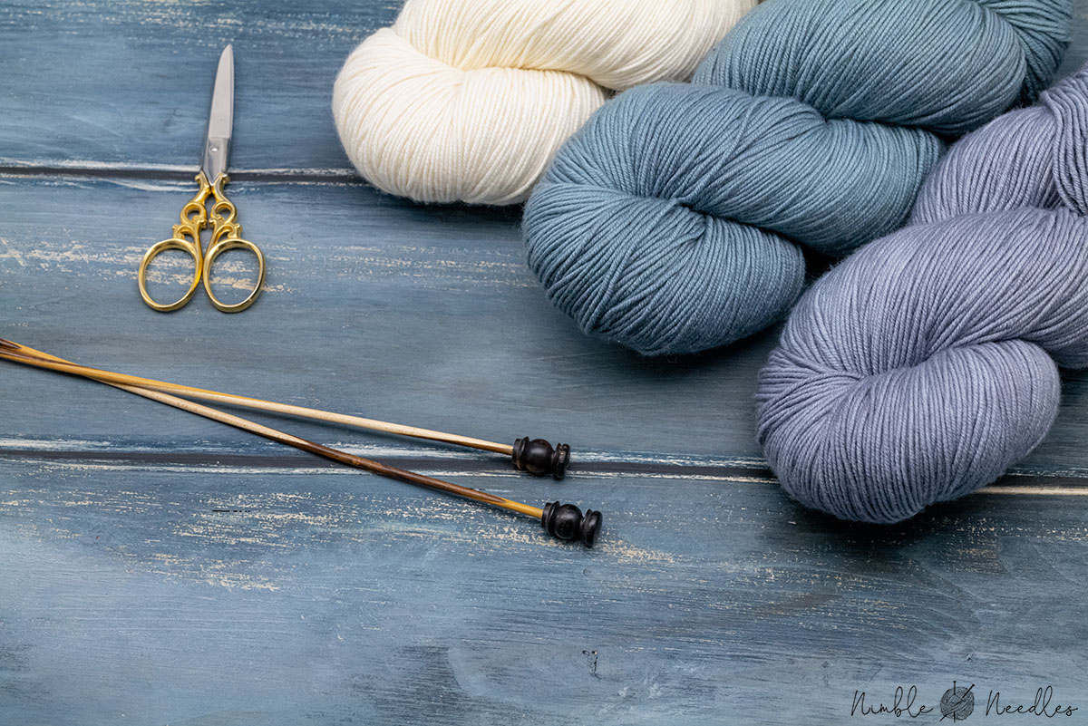 different skeins of double knitting weight yarn on a wooden board with a scissor and knitting needles