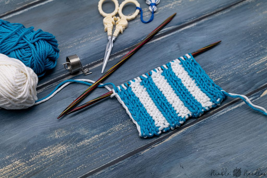 a swatch in double knittin ribbing in white and blue on a wooden board