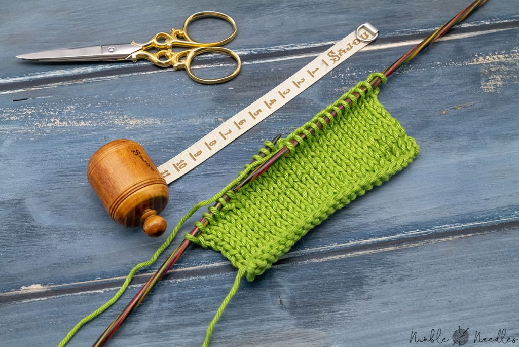 knitting a swatch to check if it is double knitting yarn and a tape next to it to determine the gauge