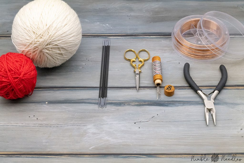 all the materials needed for this tulip knitting pattern on a wooden board