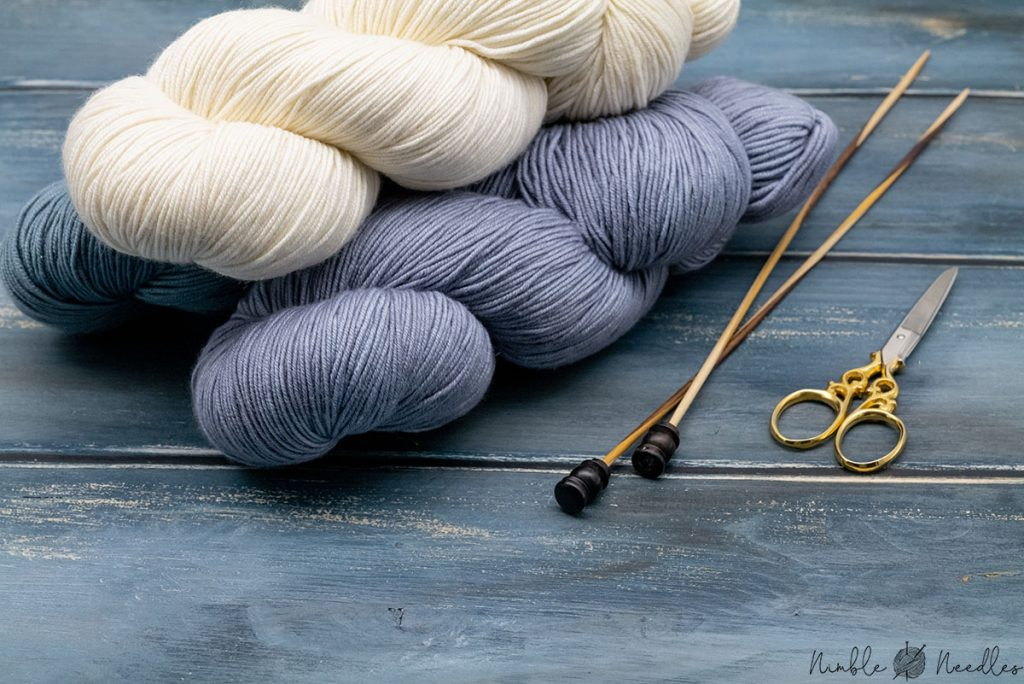 three skeins of double knitting yarn in different colors on a wooden board with knitting needles next to it