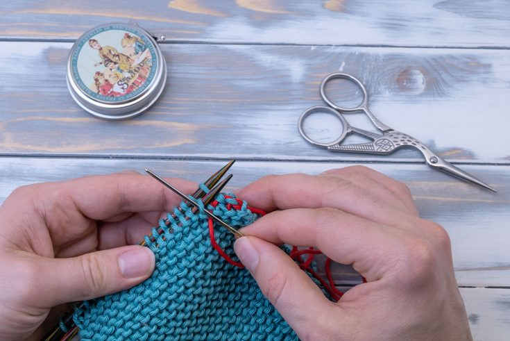 someone grafting garter stitch to close a horizontal seam with a tapestry needle