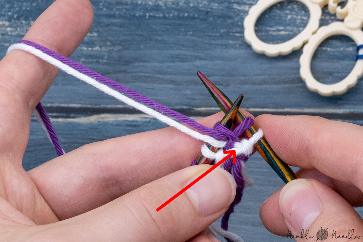 trapping the twisted stitch as you purl the next stitch with yarns in front
