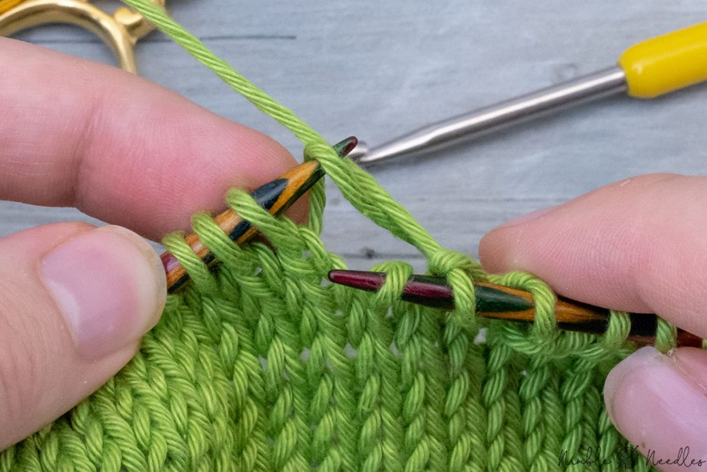 pulling the strand/stitch out with your left knitting needle