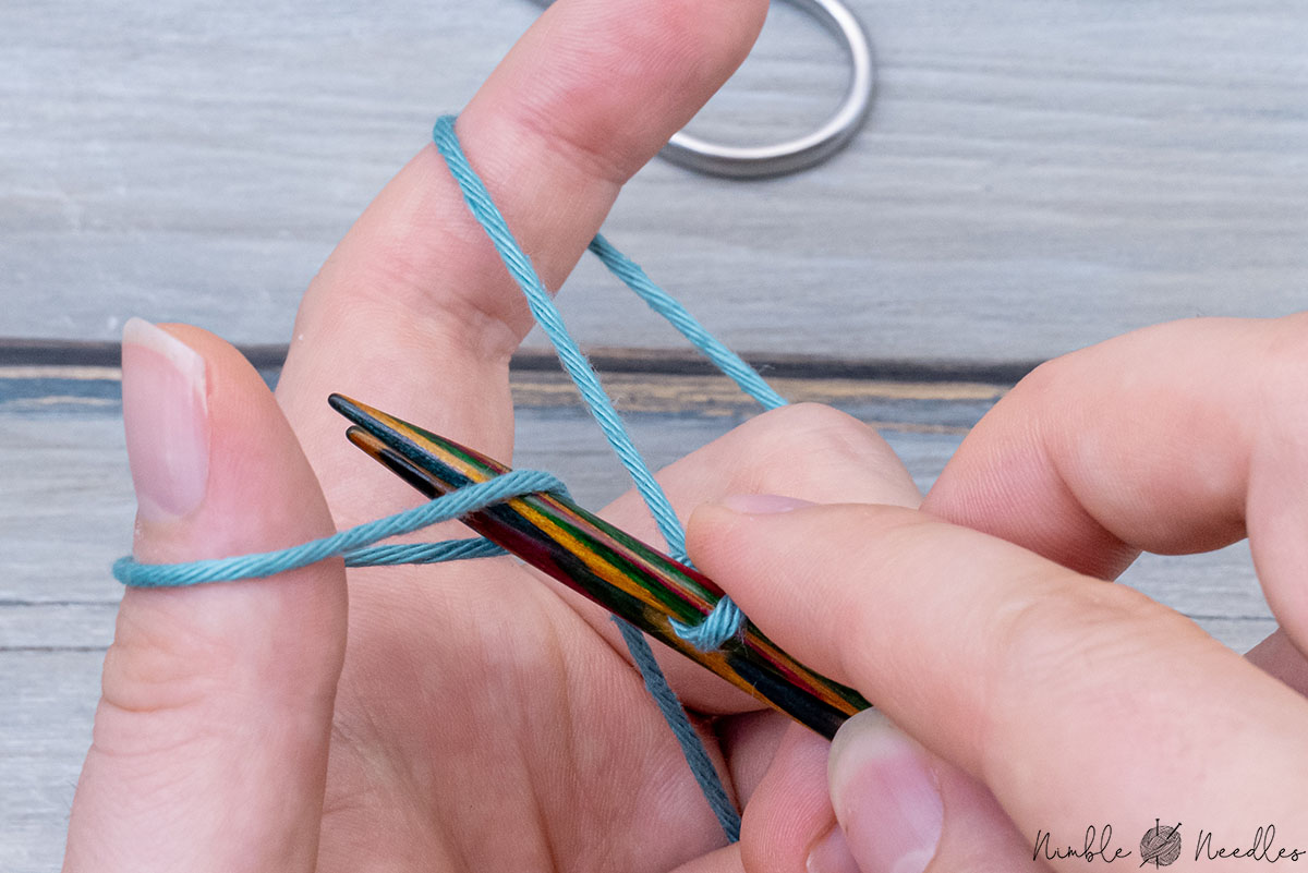 inserting both needles into the loop around the thumb at the same time