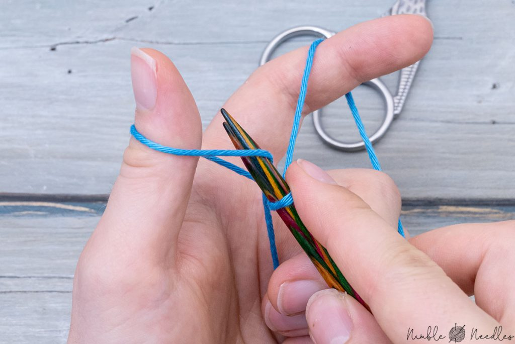 inserting both needles into the loop around the thumb