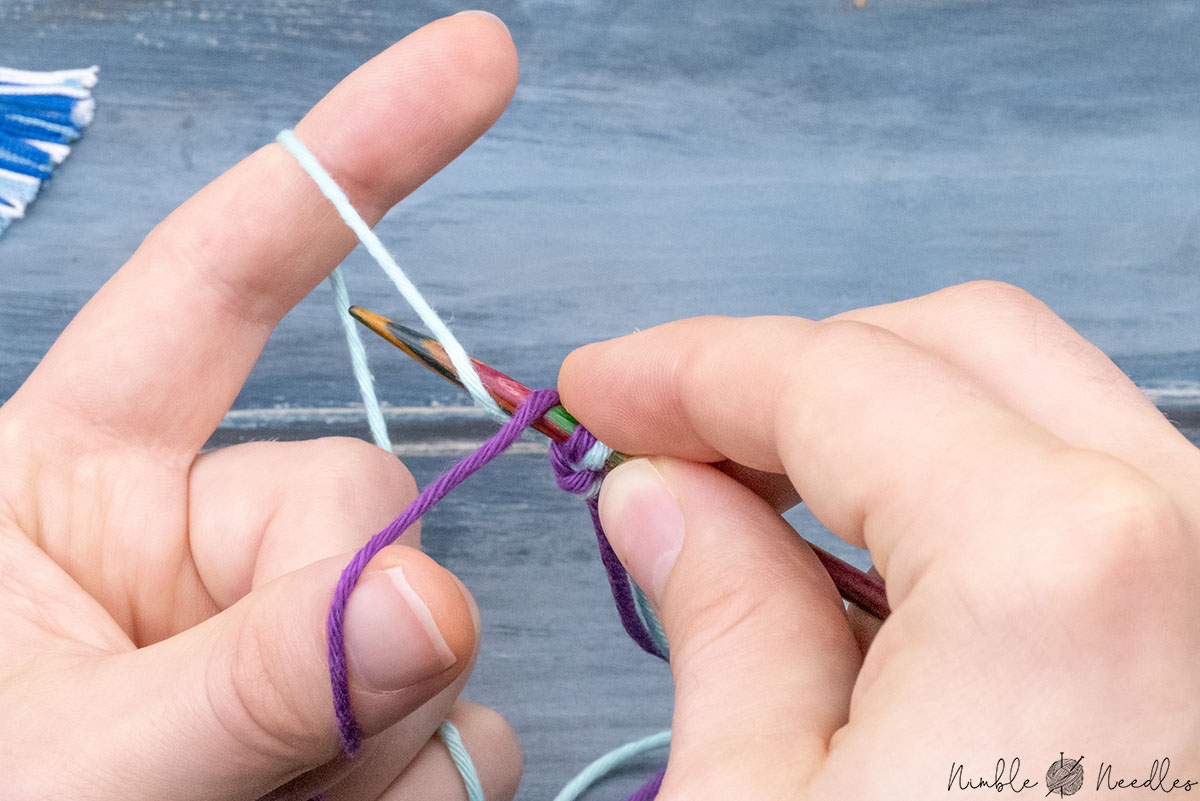 garbing the yarn towards the index finger from above
