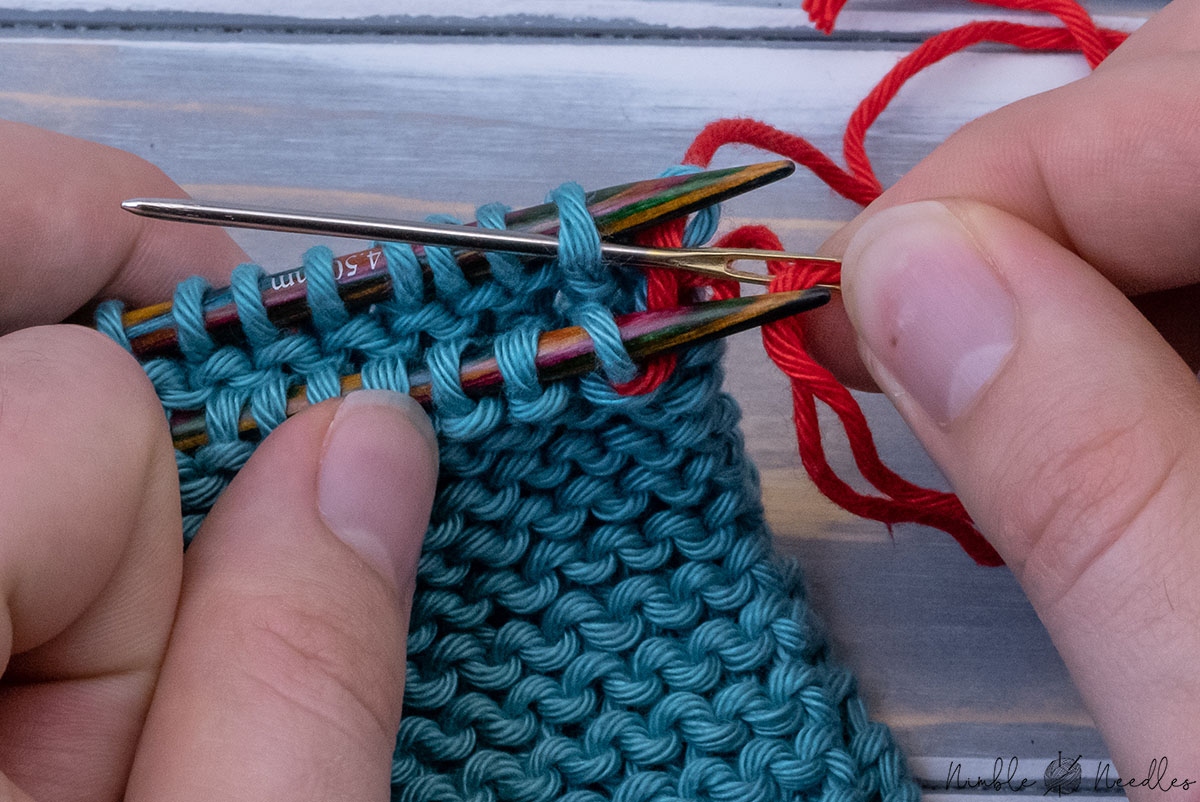 pulling the yarn through the second stitch on the back needle purlwise