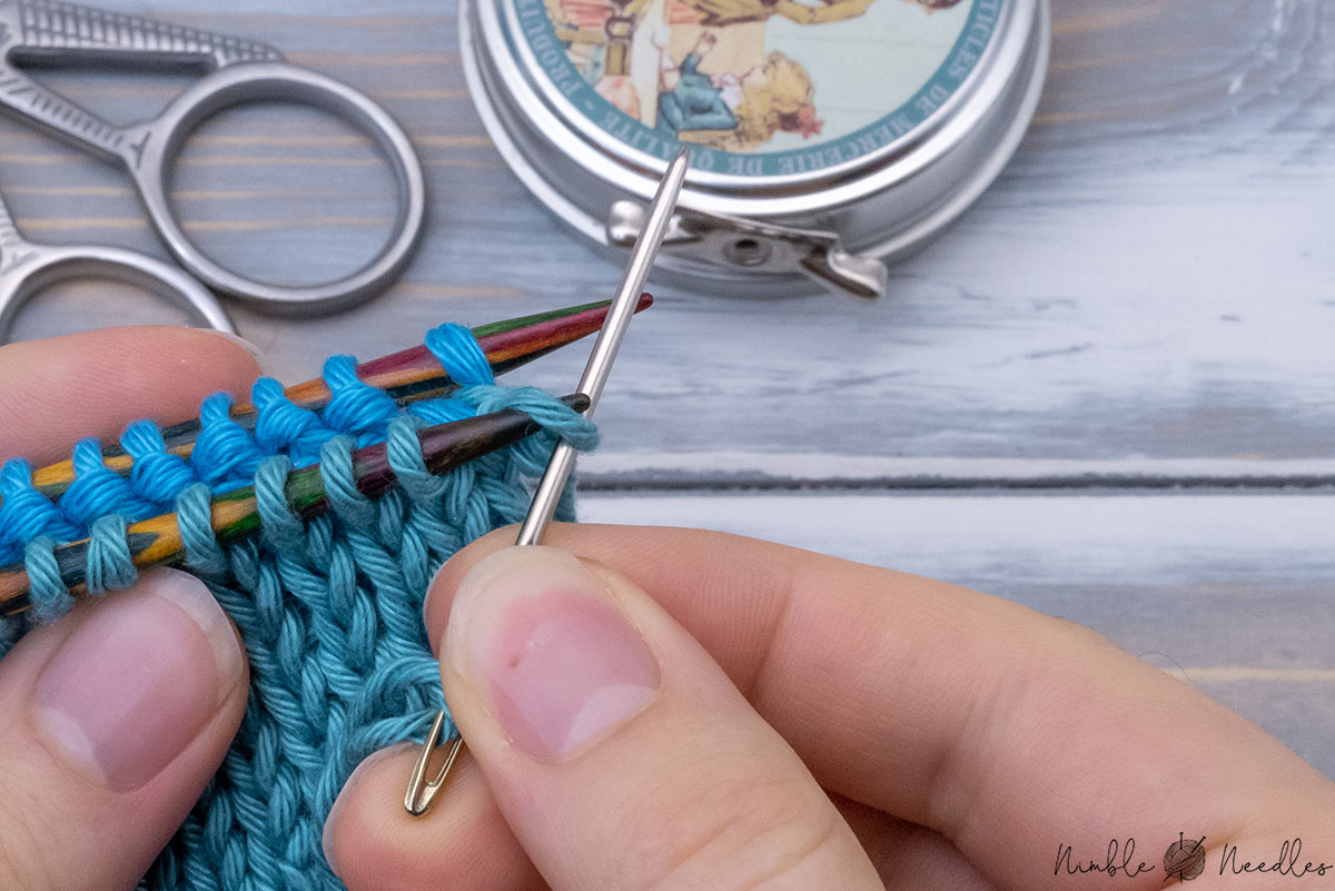 pulling the yarn through the first stitch on the front needle knitwise and dropping it off the needle at the same time