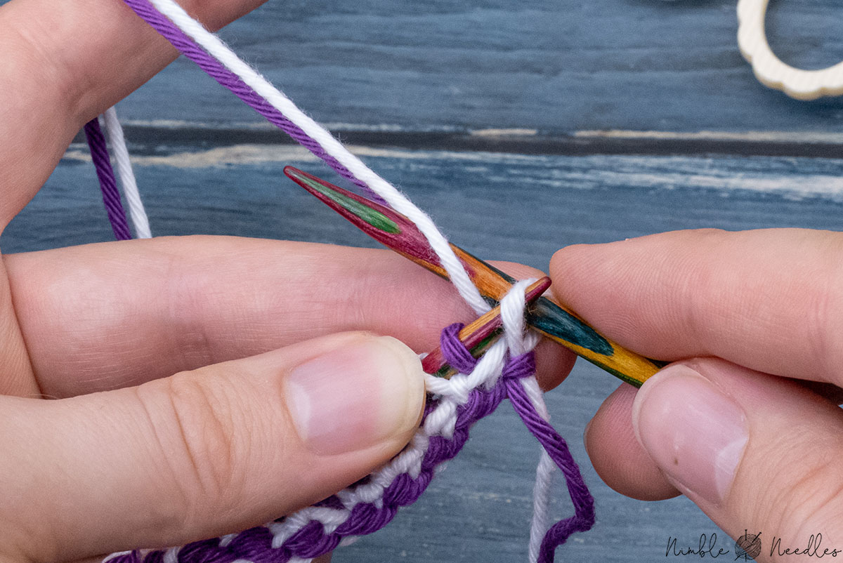 having turned the work around, knitting one stitch through back loop with yarns in back