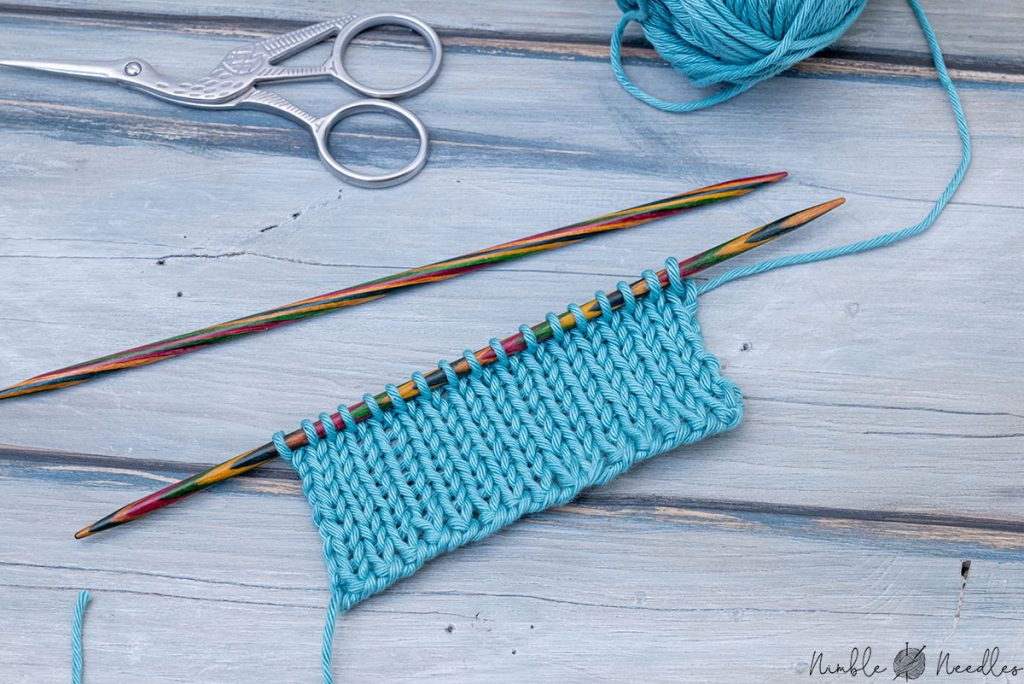 swatch in stockinette stitch with a two needle cast on edge lying on a wooden board