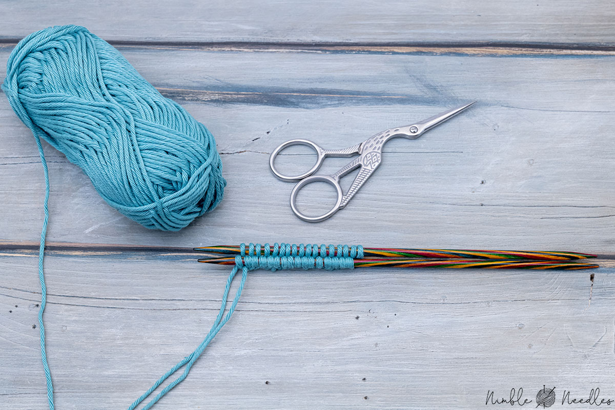 a two needle cast on with various knitting tools on a wooden board