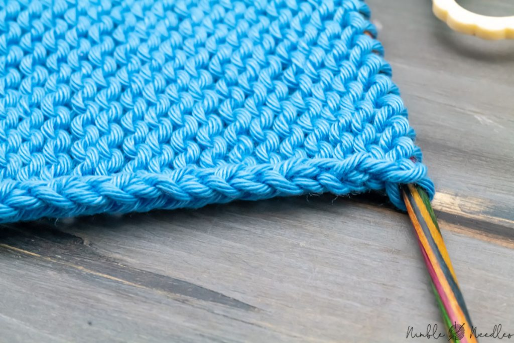 a close-up of a standard edge created by knitting stockinette stitch