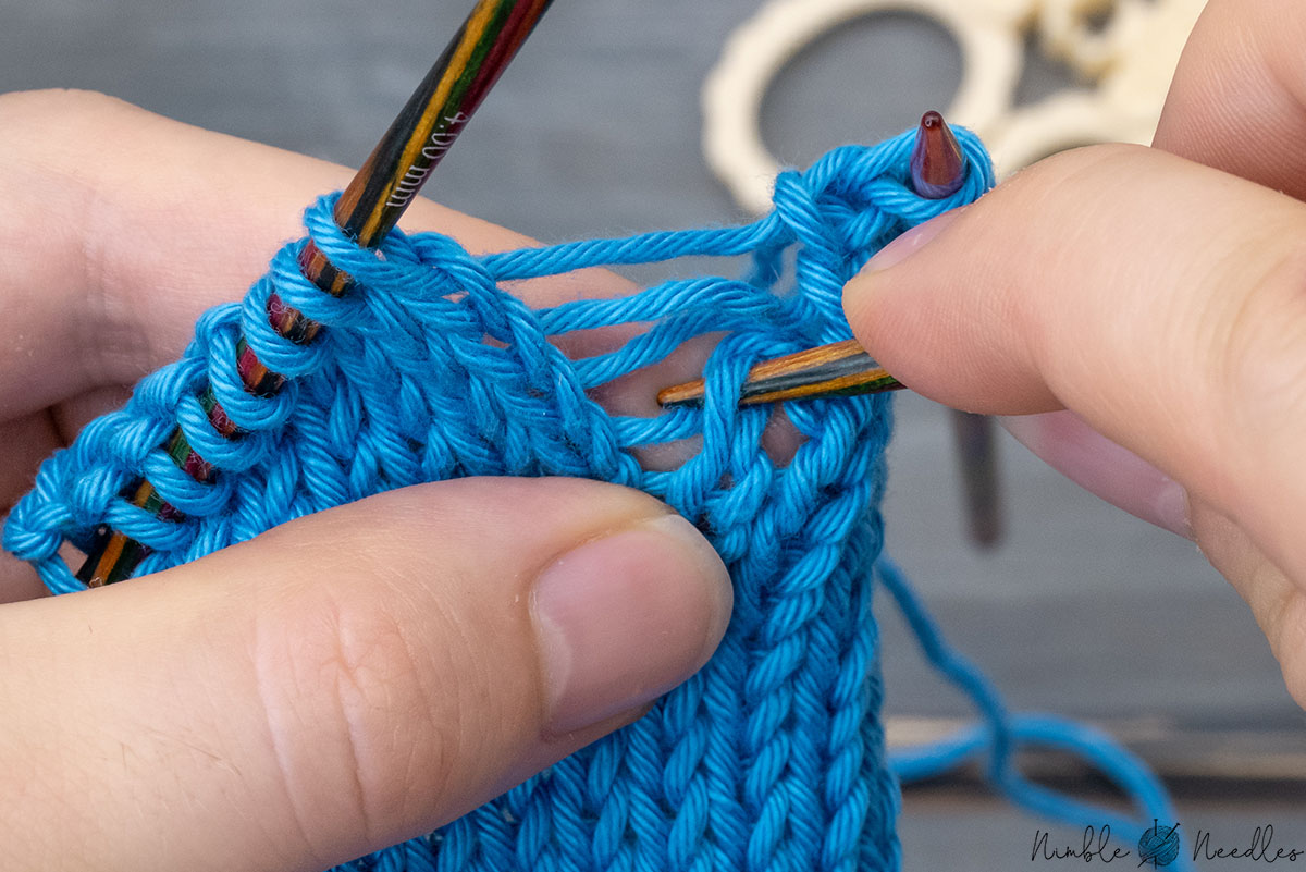 fixing a dropped stitch without a crochet hook using the index finger as a surface