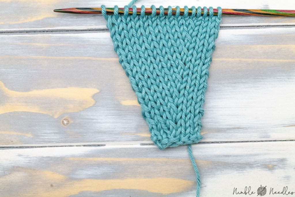 the right lifted purl increase as seen from the right side on a knitting swatch