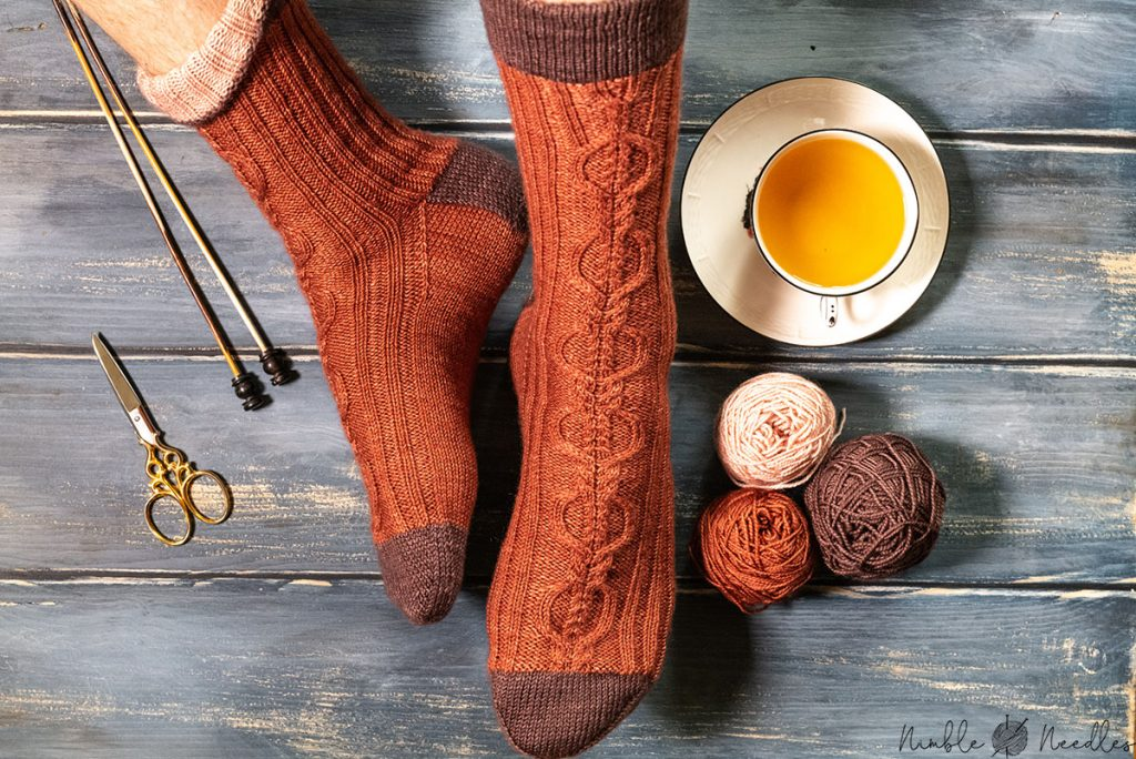 a beautiful cable knit sock pattern modeled on feet so you can see all sides
