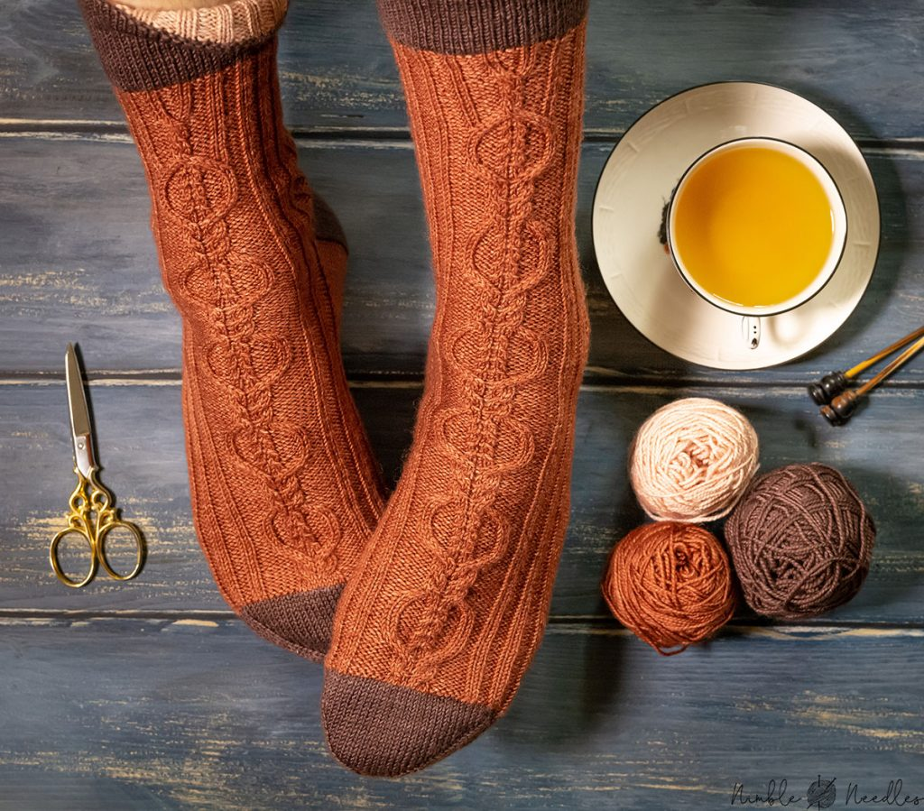 a free cable knit socks pattern for men modeled on feet