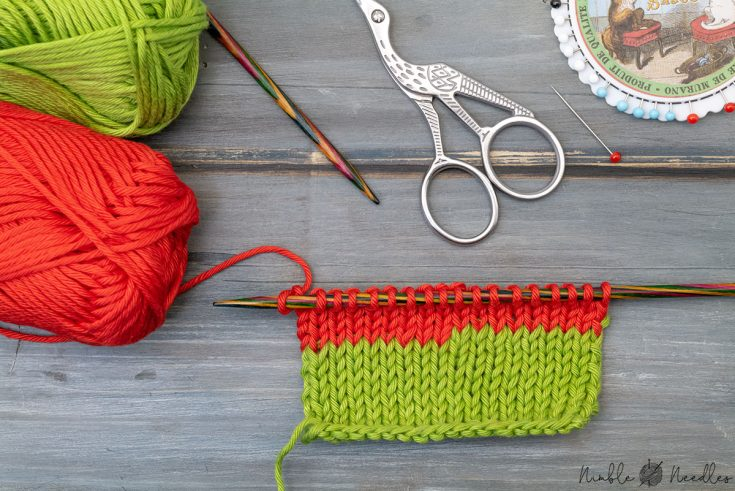 a knitted swatch where someone changed colors with the back join and various knitting tools in the background