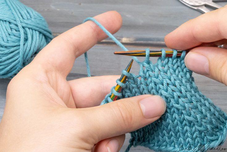 someone knitting the skp knitting decrease in teal cotton yarn