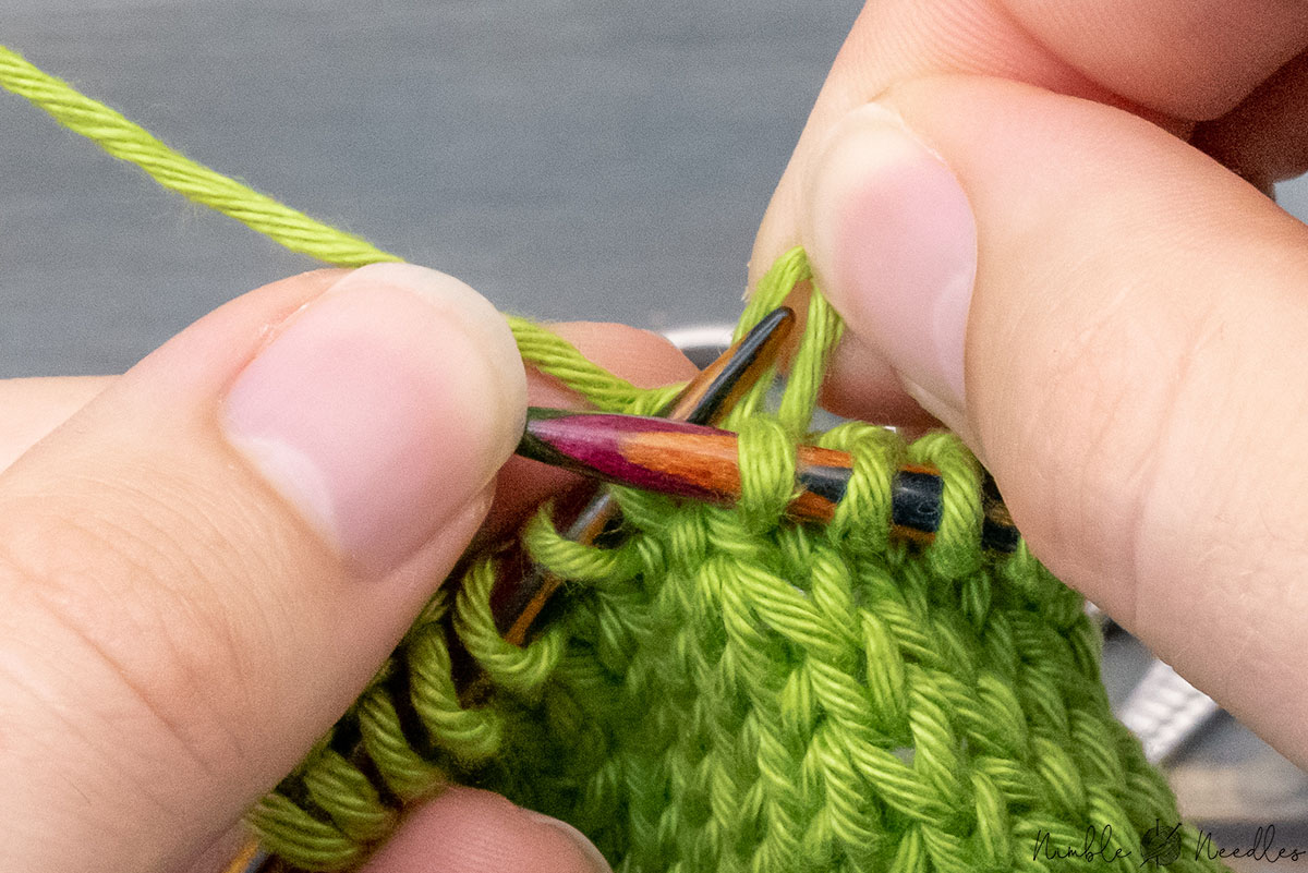 dropping the first stitch on the left needle manually with the fingers of the right hand