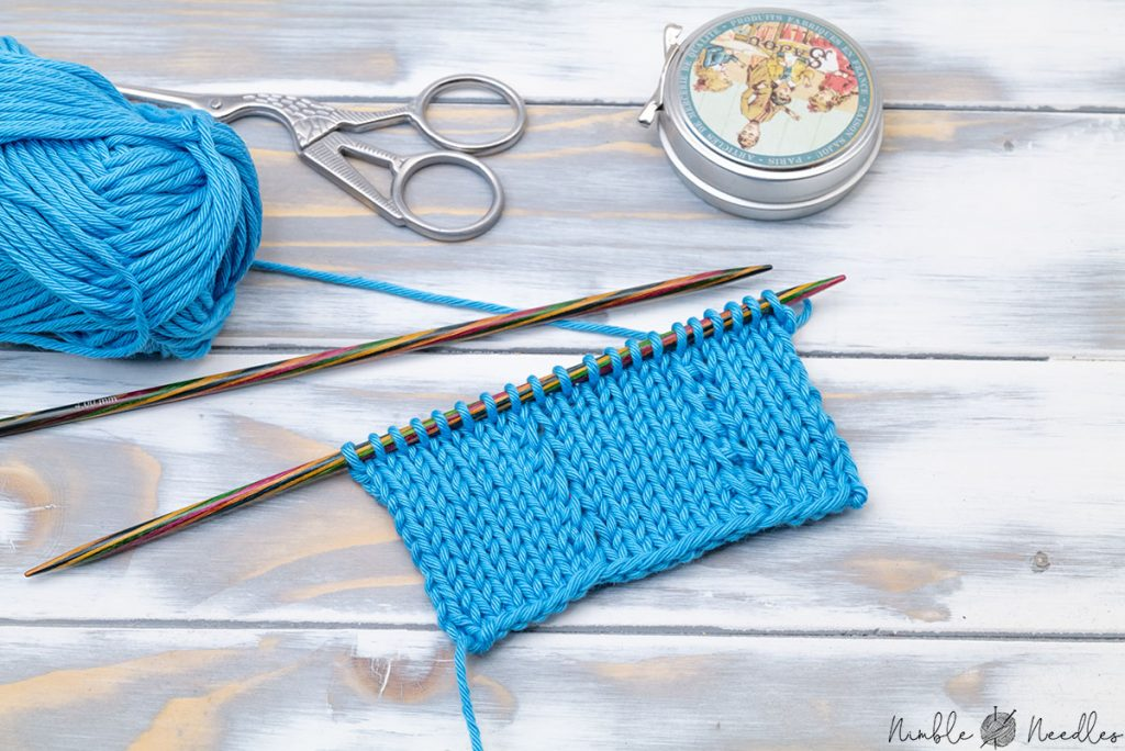 A knitted swatch with k1tog rl and k1tog ll still on the knitting needles