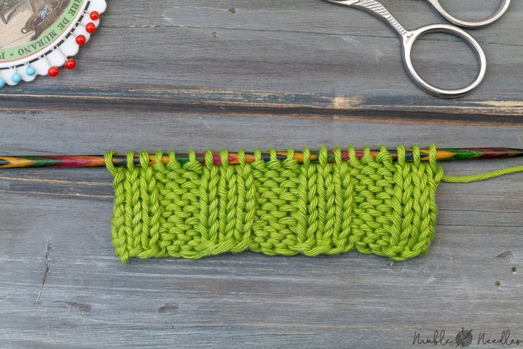 close-up of the edge of a german twisted cast on purl shown with a swatch of 3x3 ribbing