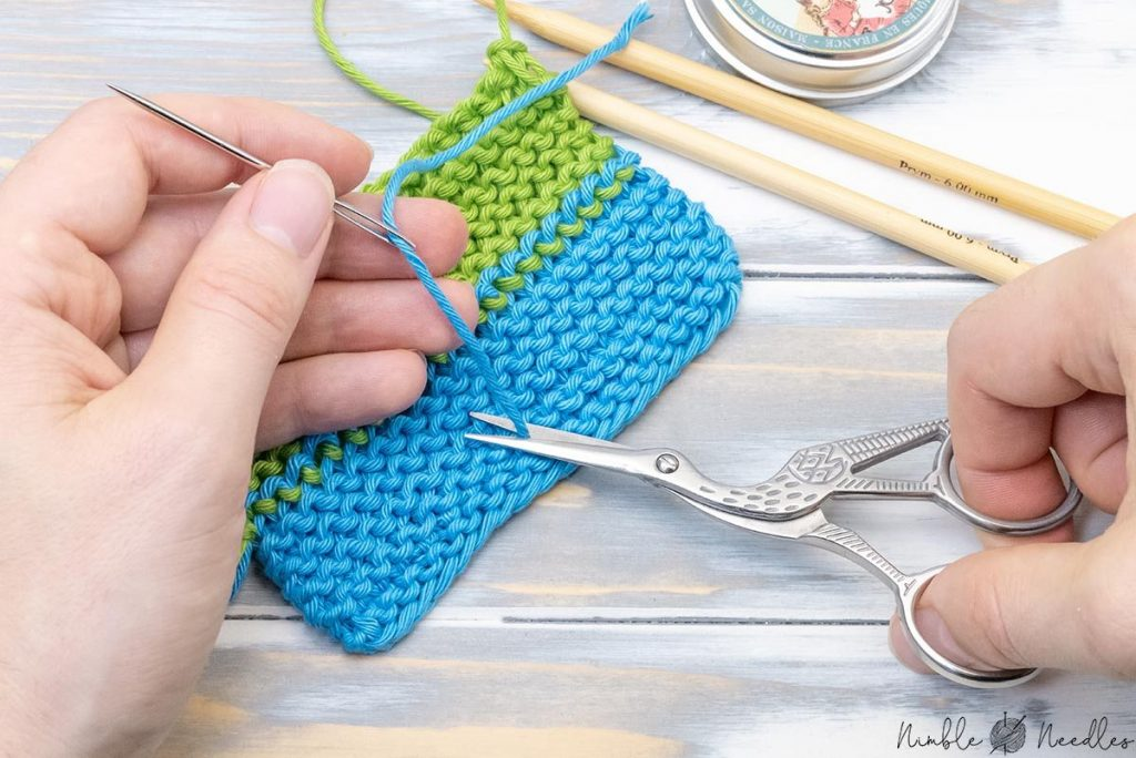 cutting away the ends with a scissor to finish knitting