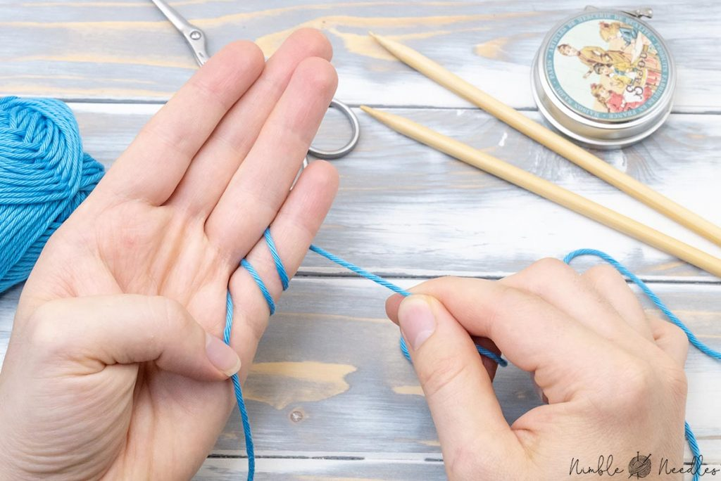 wrapping the yarn around the pinky finger two times to start knitting
